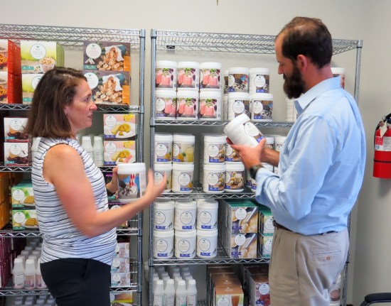 Cramer Miller gives his wife Annie a hand in restocking Medi Weightloss products at their McAllen center.