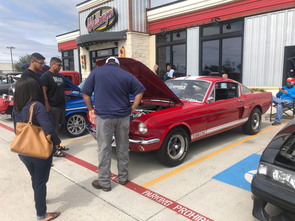 Visitors admire a Shelby Mustang engine.