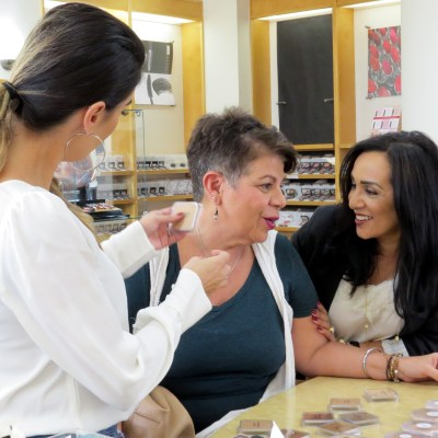 Edna Posada enjoys a quick conversation with customer Irma Burr as make-up artist Yvette Hinojosa matches the foundation best suited for her at Spa La Posada's Matte About Hue event Oct. 15 in McAllen.