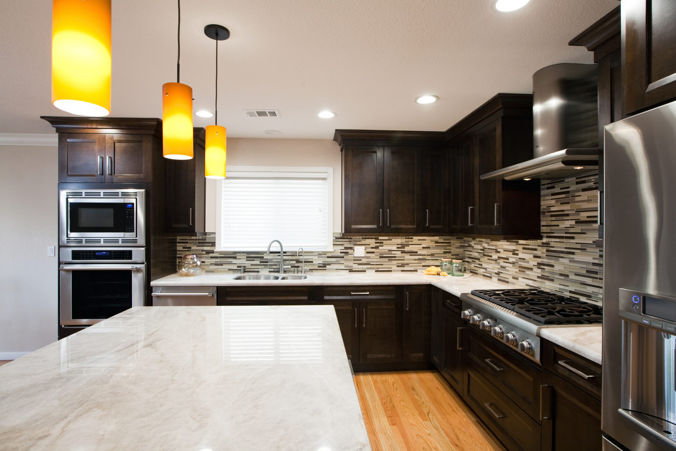 A modern kitchen with stainless steel appliances, tile back splash, and granite counter tops.