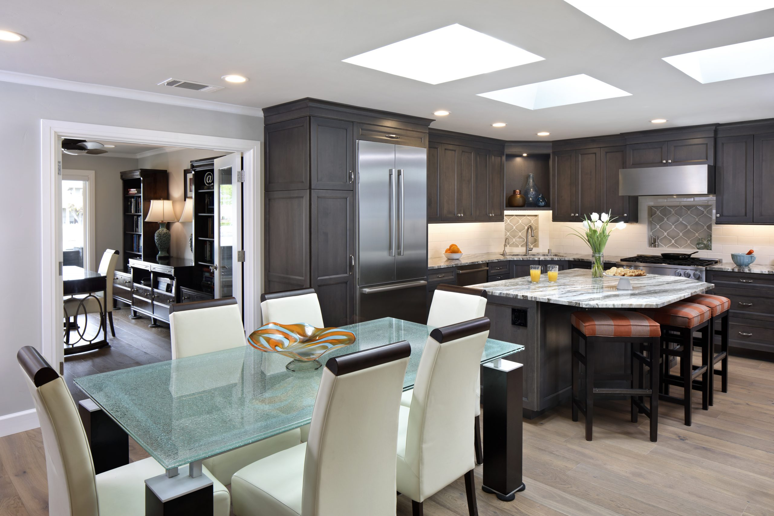 A kitchen and living room combination with a large granite island and glass table.