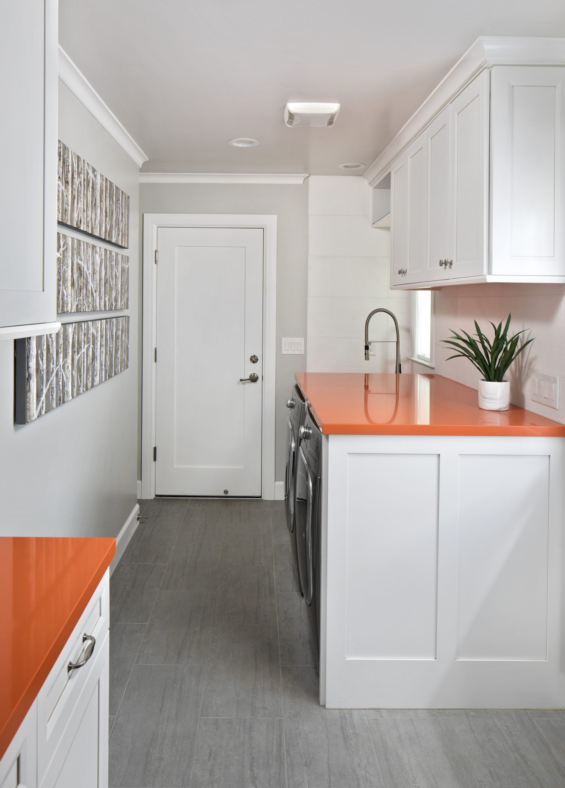 A laundry room with orange counter tops and modern appliances.