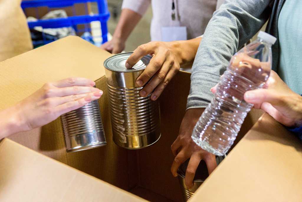 Unrecognizable food bank volunteers organized donated items