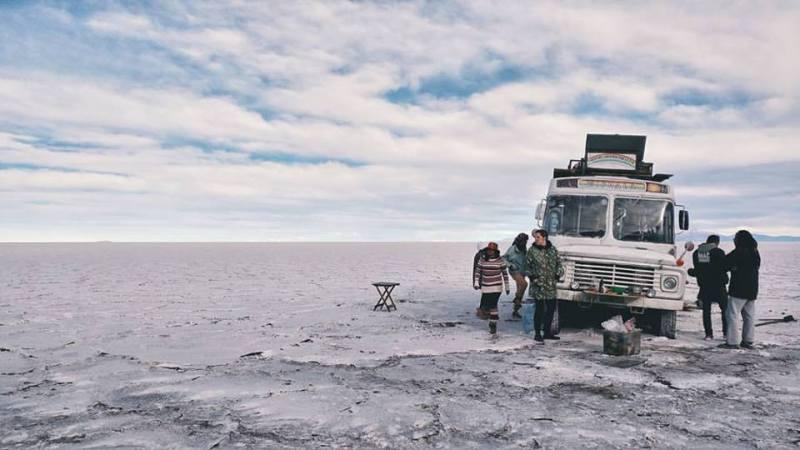 Grupo de pessoas envolta de um ônibus no Salar do Uyuni - Destinos não convencionais