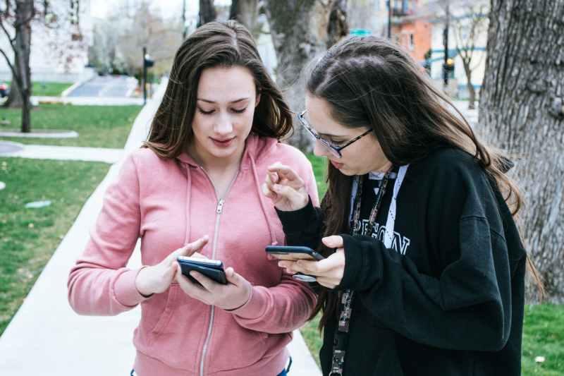 Duas mulheres com telefones celulares nas mãos - Internet móvel na Viagem