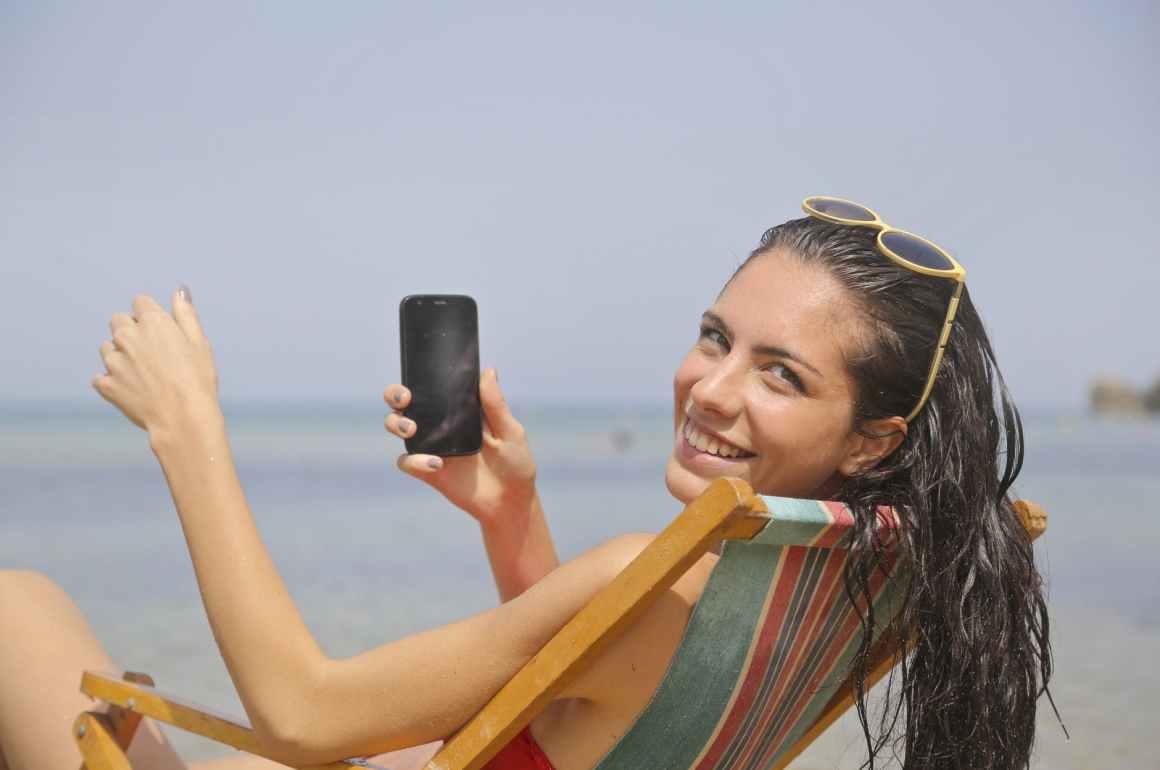 Mulher na praia segurando um telefone celular.