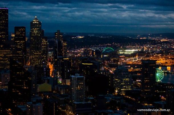 Seattle Great Wheel y el estadio CenturyLink iluminados.
