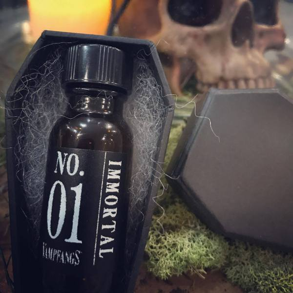 An Apothecary bottle of Vampfangs Fragance: Immoral #1 with a Black Handmade Coffin Box - Background set of human skull and a glowing candle.