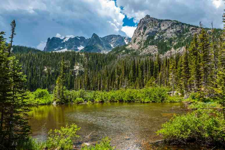 Beautiful sky over Fern lake with view of Gabletop, Knobtop and Notchtop mountain peaks in colorado