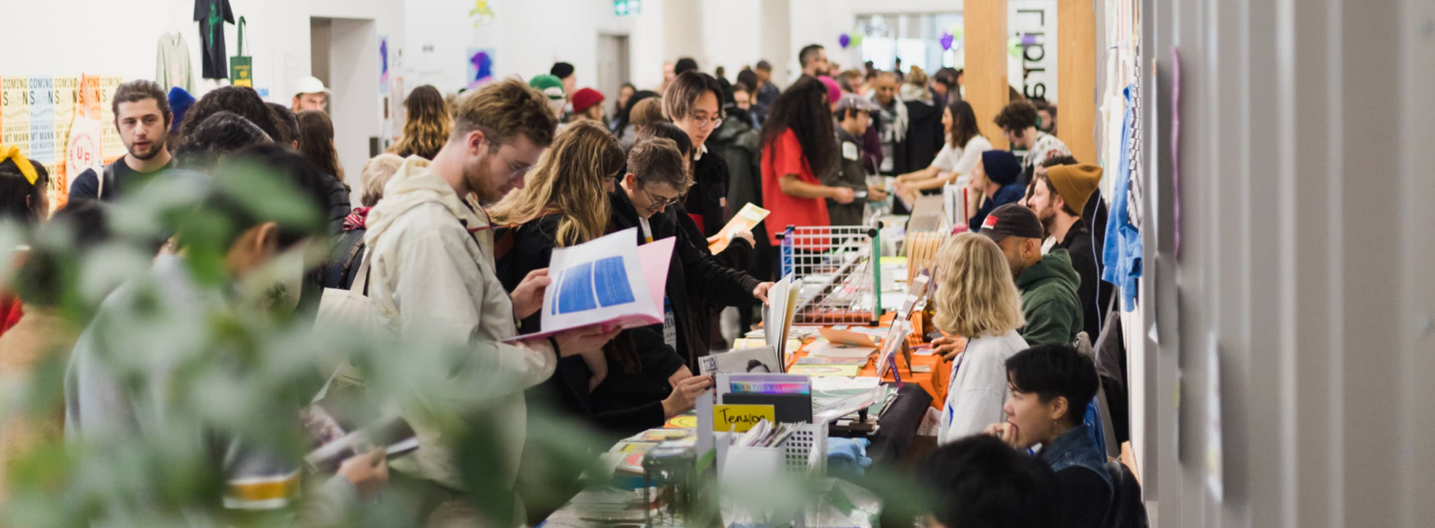 Photograph from VABF 2019 of the Vancouver Art Book Fair hallway at Emily Carr University, attendees look at exhibitor tables, a plant is out of focus in the foreground.