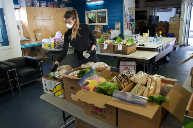 An indoor image of person wearing a mask while filling boxes of food
