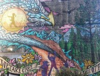 "An image of the mural at Strathcona Community Centre with a painted banner reading: ""We take care of the earth"""