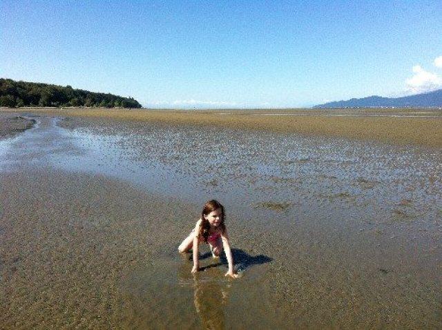 Girl playing at low tide at Spanish Banks