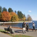 People walking along the Stanley Park Seawall in the fall
