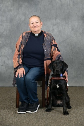 A person with shavd head, wearing a clerical collar is seated.  A black lab is at their side and is wearing a harness for assistance dogs.