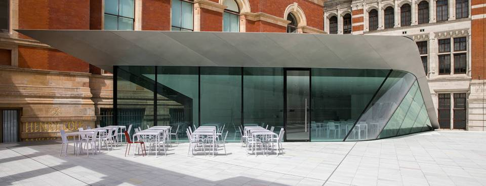 Sleek glass front of Sackler Courtyard cafe with white tables and chairs outside V&A