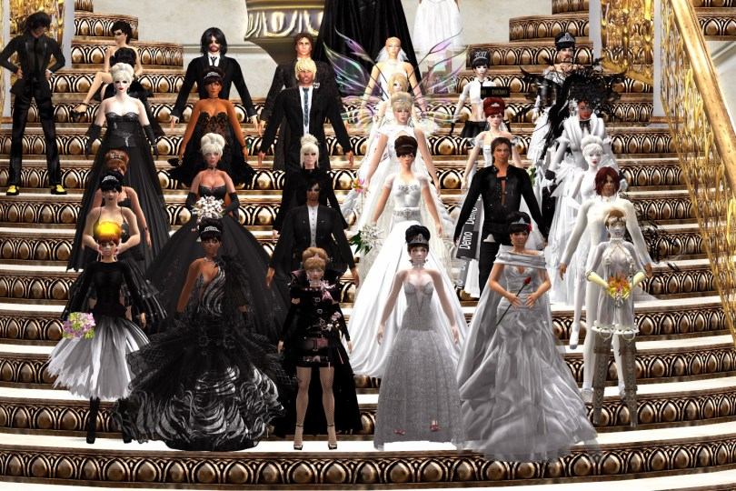 Bride Vanessa Blaylock, Groom Ze Moo, and their wedding party stand on the staircase of the Grand Ballroom, Covent Garden, London. The women are all dressed in white and the men are all dressed in black.