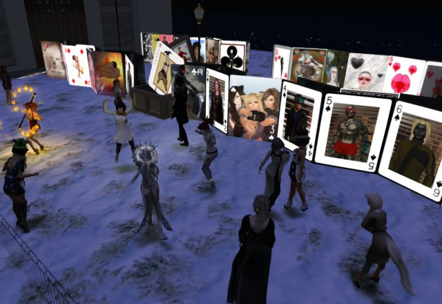 opening reception for avatar card deck. Avatars stand around and look at a giant deck of life-sized playing cards, each featuring a different selfie