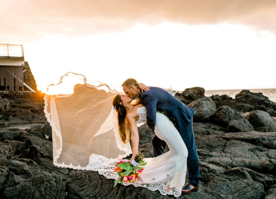 dip pose of wedding couple at sunset on cliffs