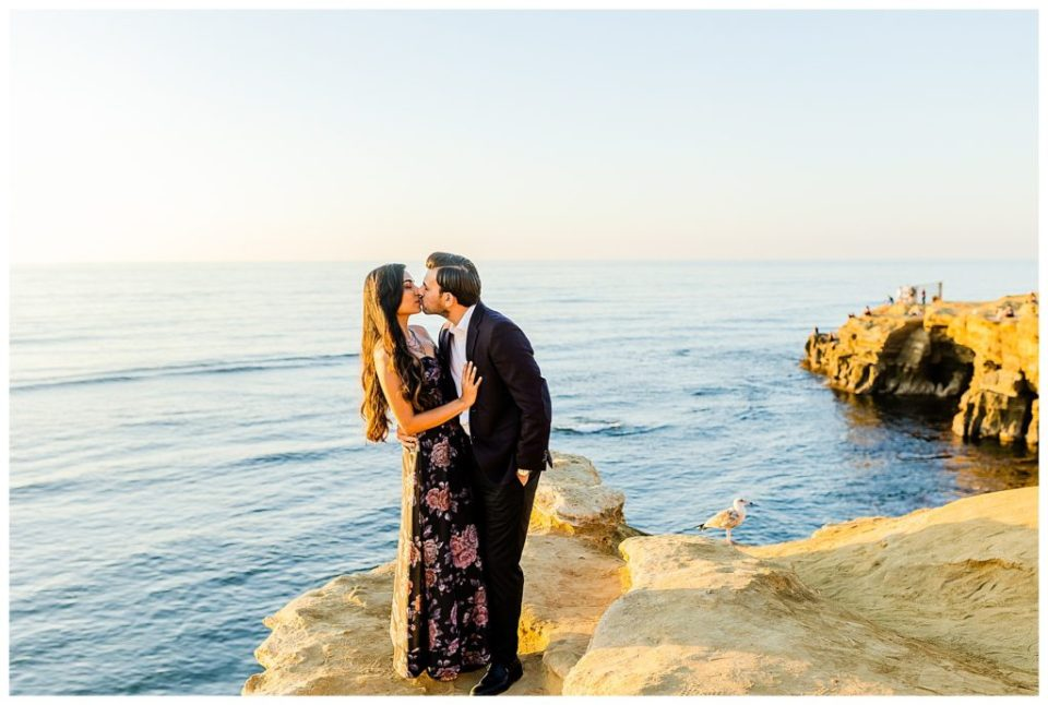 couple kissing at cliffside engagement session