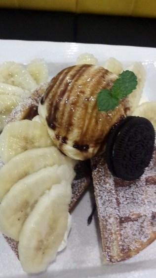 Waffle with banana, whipped cream, and ice cream