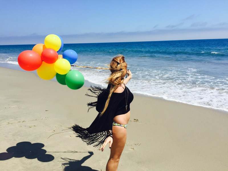 wanderlust girl on beach with balloons