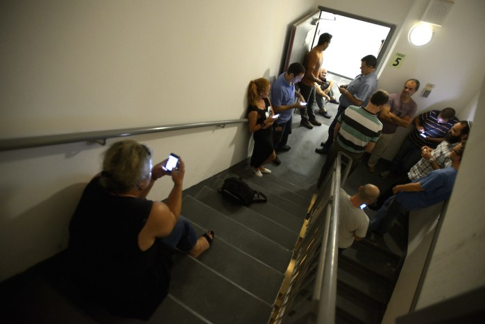 Israelis take cover in a stairway of an offices building as a Code Red siren sounds warning of incoming rockets in Ra`anana, July 13, 2014. Over 500 rockets have been fired from Gaza at Israel over the past six days. Photo by Gili Yaari