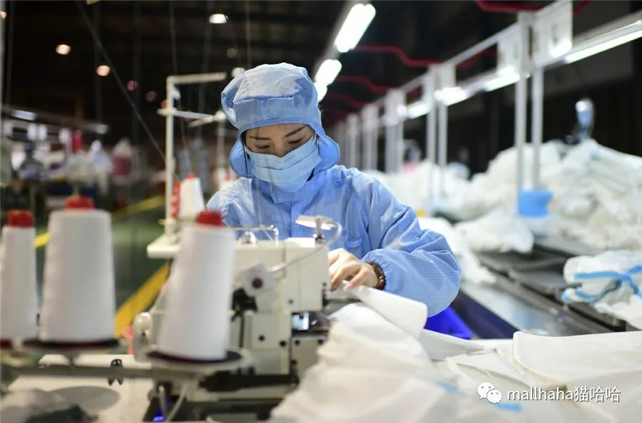 Workers produce medical shoe coverings at a company in the Bishan district of Chongqing on Feb 23, 2020. [Photo/Xinhua]