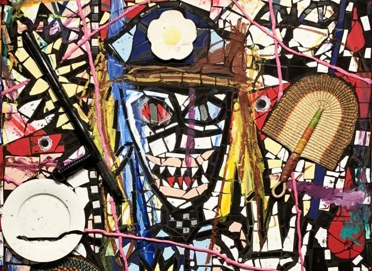 """A bright and colorful mosaic made of ceramic shards, woven grass fans, and string. The mosaic depicts an abstract portrait of a sharp toothed police officer with one hand raised in a """"stop"""" gesture."""