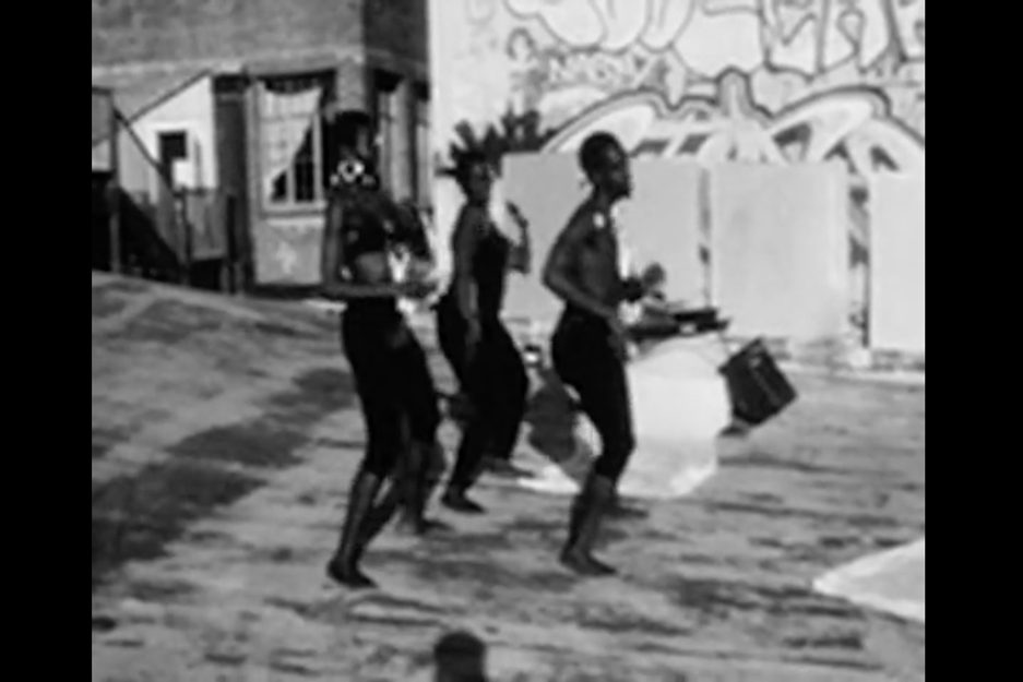 A black and white video still of three Black people, two women and one man, dancing on what looks like a city building rooftop.