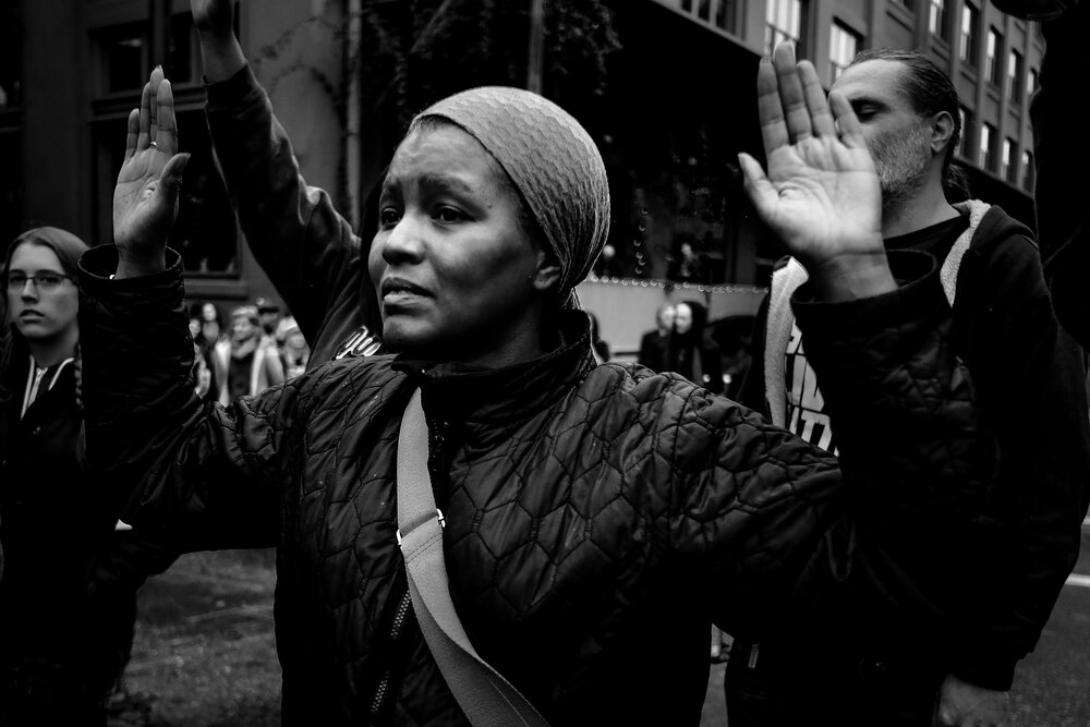 A black and white photograph of a Black woman standing in the street with both hands in the air. Her face has an expression of determination and grief.