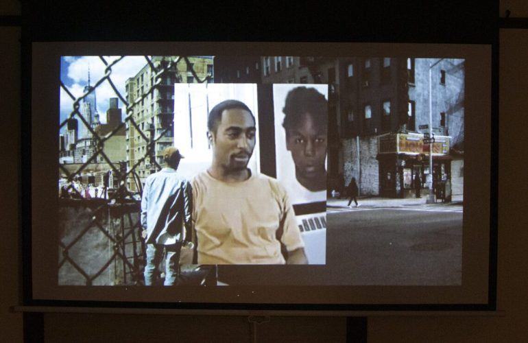 An image of a film projecting on a pull down screen. The image shows a collage of moments; a Black man in a denim shirt, jeans, and a baseball cap stand in front of an image of rapper Tupac sitting, his mouth slightly open as though in mid-sentence, with a photograph of a Black boy behind him. In the background on the left, we see the New York City skyline behind a chainlink fence. On the right, we see a New York street corner with a liquor store.