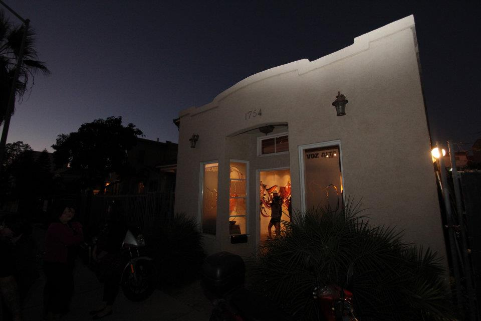 "A photograph of a residential building at dusk. The sky is almost dark but glows blue around silhouettes of palm trees. The house is white plaster, and an orange light glows through windows. The words ""Voz Alta"" are barely visible at the top of one window. A man stands inside the space with art hung on the walls."