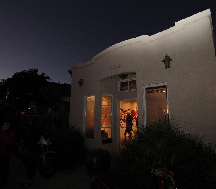 """A photograph of a residential building at dusk. The sky is almost dark but glows blue around silhouettes of palm trees. The house is white plaster, and an orange light glows through windows. The words """"Voz Alta"""" are barely visible at the top of one window. A man stands inside the space with art hung on the walls."""