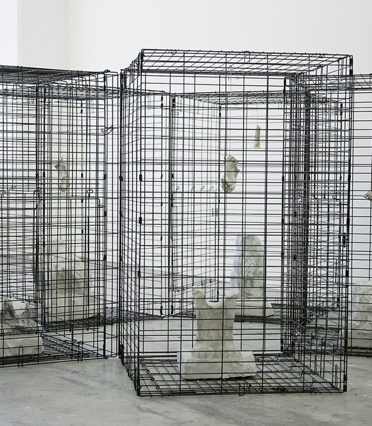 An installation view of a sculpture by Harold Mendez. Five vertical black cages are arranged in a hexagon. Each cage contains abstract, yet corporeal plaster sculptures of varying sizes.