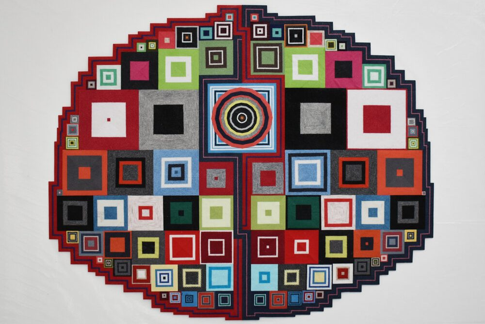 An oval with angular edges made up of many, multi-colored squares. Each shape has at least one inner square of a different color. There is a line down the center of the piece interrupted with a square that contains increasingly smaller squares and a circle filled with many other circles in the center.