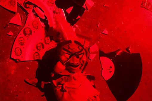 Shattered vinyl records and other debris litter a floor flooded with red light. A mask with a devilish smile sits on top of the pile of broken items.