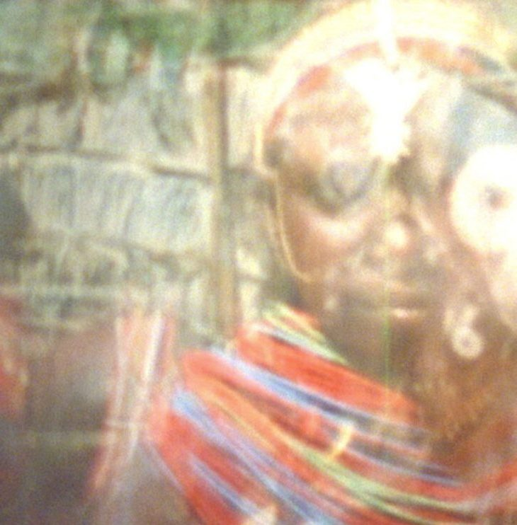 A still of a film by Christopher Harris. It shows a Black man's face looking into the lens, with layers of light lines floating across the frame, and a large blown out bright spot covering the person's left eye.