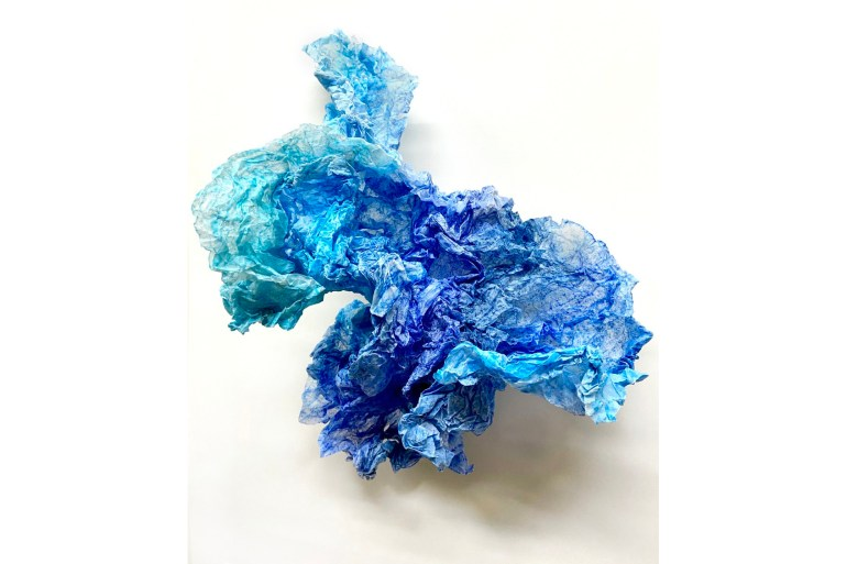 A crumpled piece of paper stained shades of blue from saturated cobalt to bright turquoise. The paper appears to have been tightly crushed, then reopened, revealing many folds.