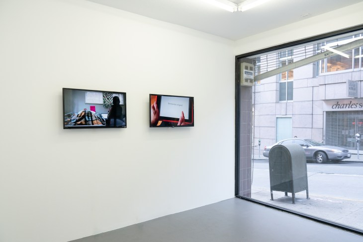 """An installation view of Patty Chang's exhibition """"Que Sera Sera"""" at Friends Indeed Gallery in San Francisco. The image shows the gallery's interior wall and floor-to-ceiling street-facing window. There is a mail drop box outside, and a Charles Schwab across the street. In the gallery, two screens playing videos hang on the wall."""