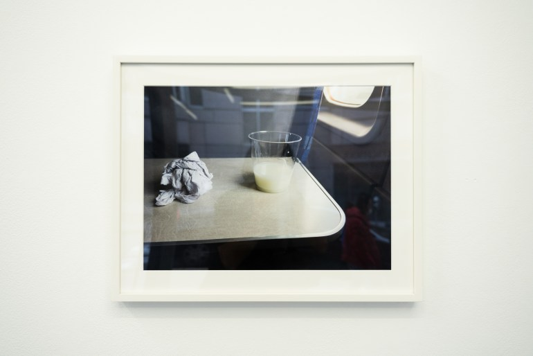 A framed and matted photograph of an airplane tray table with a small clear plastic cup full of a thick white substance. There is a crumpled napkin to the left of the cup. The seat is by the airplane window, and cool, diffused light illuminates the scene.
