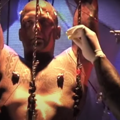 """A video still of a recording of Ron Athey's performance """"St. Sebastian."""" Athey is suspended by ropes hooked into his flesh, another person wearing latex gloves inserts a long, thin metal rod into his bicep. Athey has an expression of entranced semi-consciousness."""