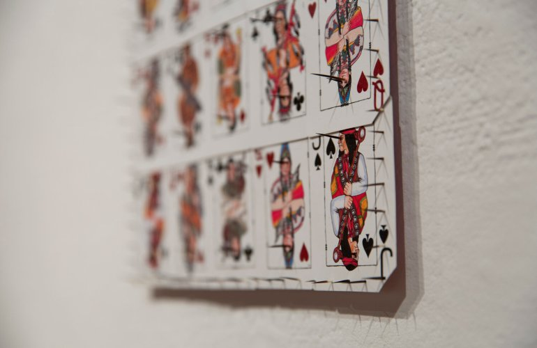 A close-up photograph of a sculpture by Emma Robbins featuring a grid of king, queen, and jack playing cards from a Fire Rock Casino deck. The figures on the cards are different Indigenous characters. The cards have a porcupine quill protruding from each face, and quills line the edge of the grid.