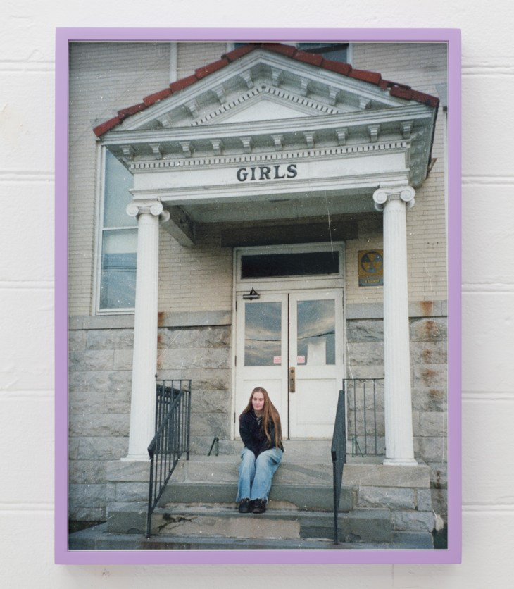 On the steps of an institutional-looking edifice, below a columned portico labeled GIRLS, sits Flood, perhaps in her very early 20s. Her face, with eyes closed, gives nothing away, but her leaning-forward posture, with arms tucked tightly between her thighs, reads as self-protective. On the wall behind her is a fallout shelter sign. The photograph is in a thin lavender frame.