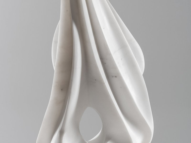 A marble sculpture that resembles a benign, almost blooming flower, but the pointed tips of the spiraled corolla mimic fingers pressed together to quickly, sharply pursue an object. Finally, above the base of the piece, there's a small hole.
