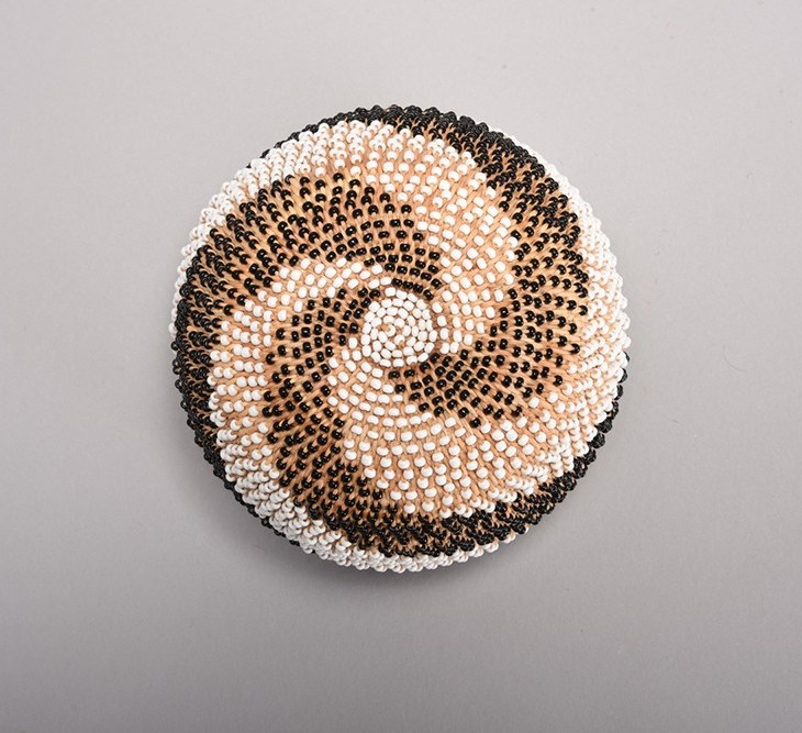 A round woven basket seen from below. The basket is covered with intricate black and white beads creating a swirl pattern emanating from the center, which is a small circle of white beads.