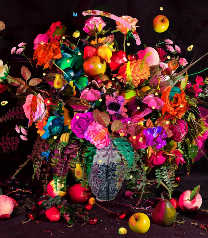 A photograph of a bouquet of flowers and fruit bursting out of a vase on a black velvet backdrop. The flowers and fruit are lit with differently colored lights. There are some digitally added marks and images superimposed on the photograph, such as various emojis.