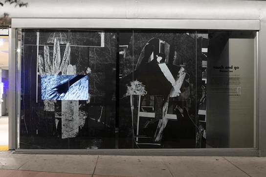 Collage of black and white photos, displayed inside a street-level room with floor-to-ceiling windows, next to a parking garage. In the background on the left, a large white hand is set against a black background, which covered in random lines. A negative photo of a hand is superimposed on top. On the right, portions of black-and-white photos are cut into the shapes of hands and arranged abstractly.
