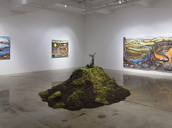 An installation image of art in a gallery with white walls and shiny concrete floor. In the center of the room there is a mound of earth covered in patchy mosses, with two small, embracing brass figure on the top. On the walls hang three large paintings of landscapes with creatures and figures in them, all rendered with a playful and surreal style.