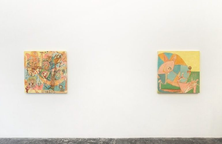 Alt text: Two square paintings hang on a white wall, above a concrete floor. On the left, a crowded painting, featuring numerous smiley faces, abstracted figures of people, animals, plants and trees. The paint used features an analogous palette of warm colors, featuring primarily yellows, oranges, blues and browns. The painting on the right works with a similar palette. Dominating most of that painting is a large circle to the left, divided by triangles of different colors and an abstract figure in the foreground. To the right of a circle hovers a smiley face next to a small rose and a human-like figure bending over. In the background, there is a plane of green grass and a yellow sky above it.